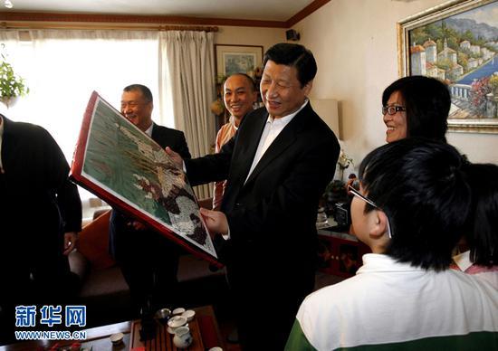 2009年1月10日,习近平来到澳门普通市民胡祖杰家中探访,了解他们生活、工作情况。这是胡祖杰一家将亲手制作的五谷杂粮画作回赠习近平。新华社记者刘莲芬摄